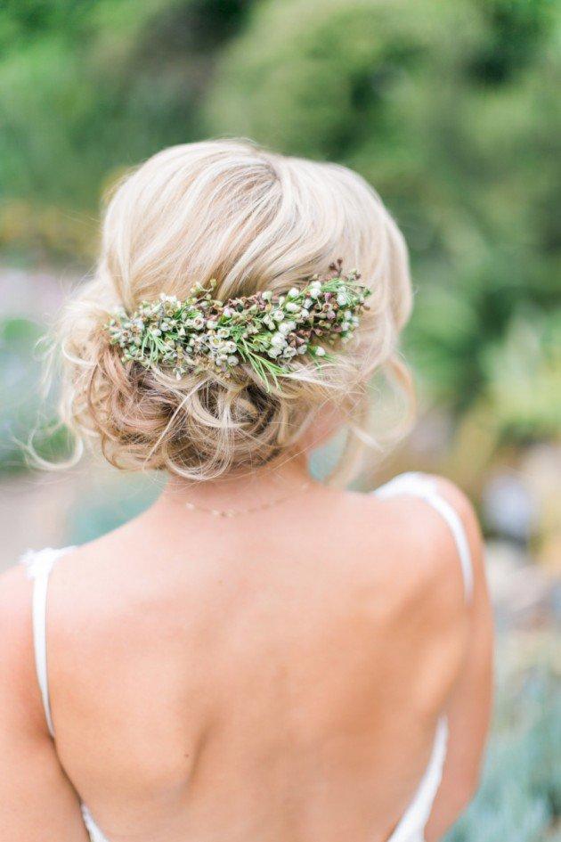 На фото: свадебная прическа - волосы уложены в пучек и украшены цветами -летний вариант прически.