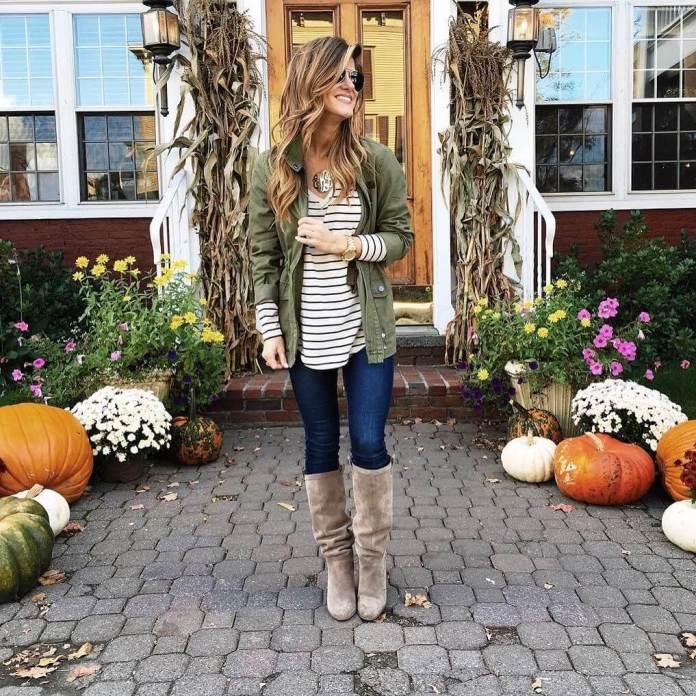 На фото: Casual стиль - белая кофта с принтом в полоску, ветровка болотного цвета, черные джинсы и высокие сапоги.