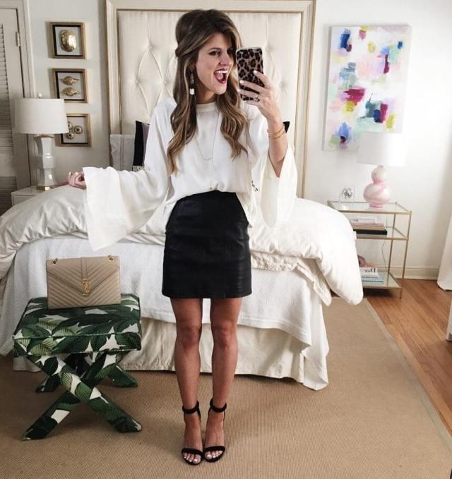 На фото: Casual стиль -  белая блузка оверсайз с черной короткой юбкой и босоножками.