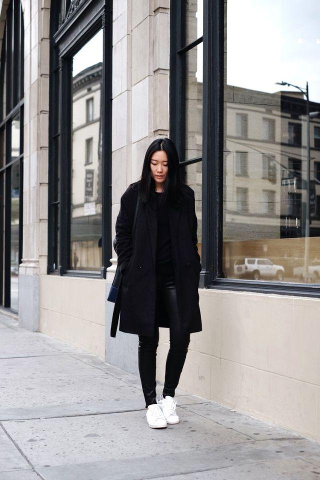 На фото: длинное черное пальто: новое красивое сочетаниес черными зауженными брюками и белыми кроссовками.
