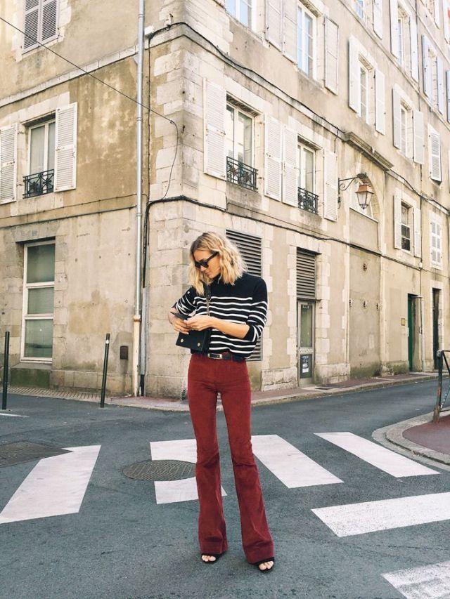 На фото: новый крутой лук на каждый день - черная блузка в белую полоску с красно коричнего оттенка расклешонными брюками.