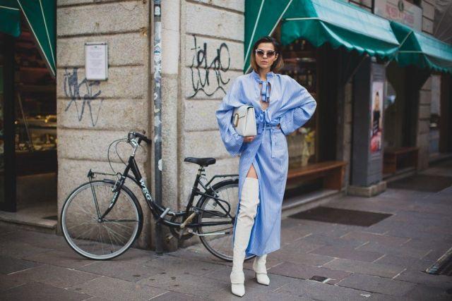 На фото: новый крутой лук на каждый день - голубой длинный плащ сбелыми брюками,сумкой.