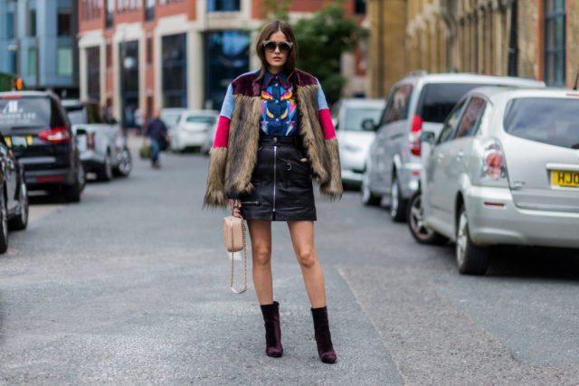 Черная кожаная юбка мини с курткой из меха и ботильонами.