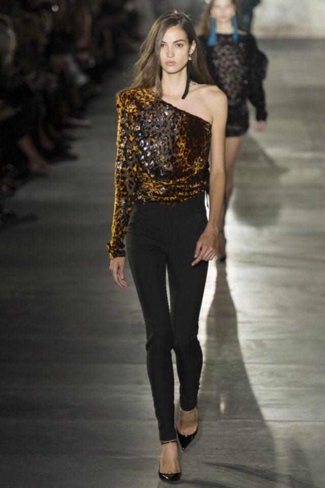 Черного цвета брюки с оригинальной блузкой с одним рукавом тигриной расветки и кожаной курткой и черные лодочки - из коллекции Saint Laurent 2017 года.