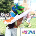 Photo of a child wearing a large, colorful paper hat