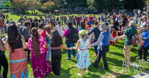Photo of a crowd of people outdoors standing in concentric circles while holding hands.