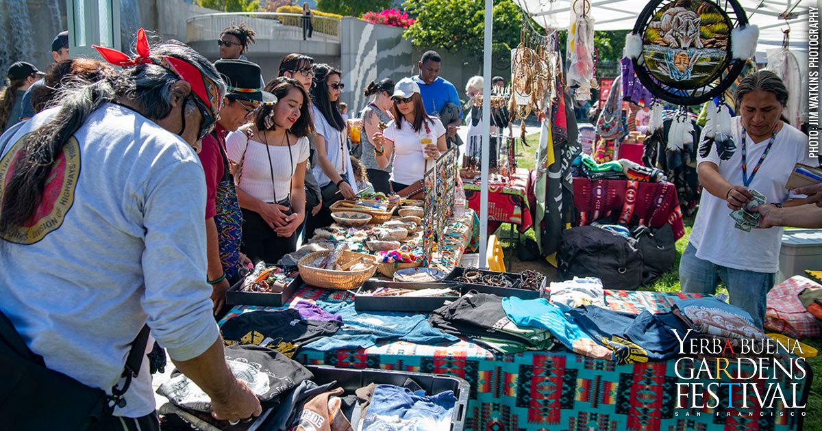Photo of people gathered around an outdoor table of various crafts by Indigenous Peoples. Photo by Jim Watkins Photography.