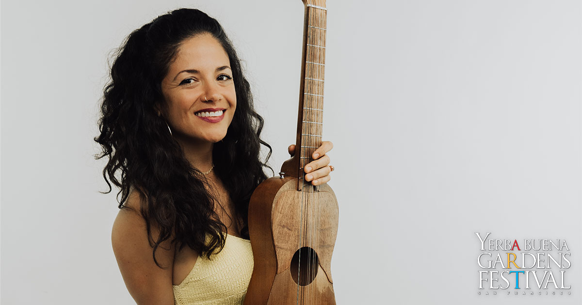 Monica Maria smiling, holding a guitar to her side with one hand