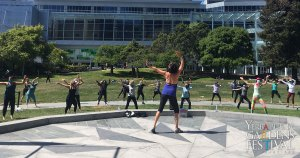 Back of a dance instructor on the Yerba Buena Gardens Festival stone stage, arms stretch upwards. Facing a group of physically distanced dance class students standing on the grass lawn, also with their arms stretch out.