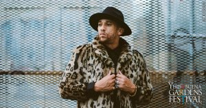 Kev Choice outside in an industrial warehouse area, against a large fence. Wearing a black fedora hat and leopard print fur coat.