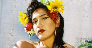 Headshot photo of La Doña in a white top, wearing big gold hoop earrings and red and yellow flowers in her hair.