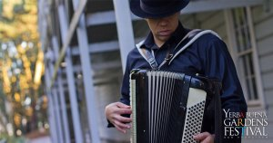 André Thierry looking down, to the right, face covered by a black fedora hat as he holds and plays and accordion