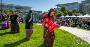 Women of Round Valley Pomo tribe in traditional clothing, dancing on the Yerba Gardens lawn, with an audience watching behind them.