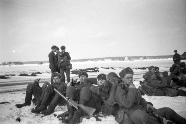 Mustavalkoinen kuva varusmiehistä istumassa lumessa tien vieressä keskellä avaraa maisemaa