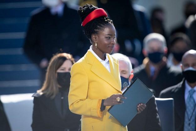 Keltaiseen päällystakkiin pukeutunut Amanda Gorman pitelee kansiota puhujalavalla, taustalla katsomossa yleisöä kasvomaskeissa