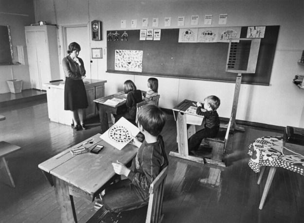Mustavalkoisen kuvan vasemmalla puolella naisopettaja seisoo luokan edessä mietteliään näköisenä käsi leukaa vasten, keskemmällä neljä istuvaa lasta katsoo opettajaan päin