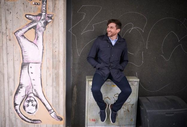 Sami Itani istuu sähkökaapin päällä ja katsoo nauraen sivuun. Itanin vasemmalla puolella graffiti, jossa mies roikkuu ylösalaisin nilkkaansa sidotun köyden varassa.