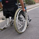 A manual wheelchair is on the road, someone is self propelling but we only see their arms