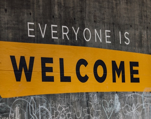 A sign painted on a concrete wall reads 'everyone is welcome'