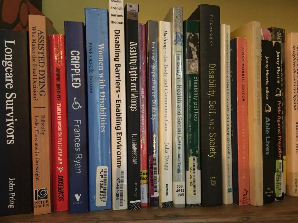 A row of books on a shelf, all on the topic of disability
