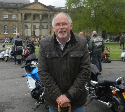 Bill stood facing the camera and smiling. There are motorcycles and large crowds in the background. Behind them is the entrance to York Castle Museum.