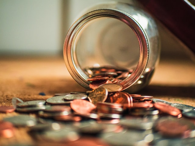 a glass jar on it's side with pennies spilling out