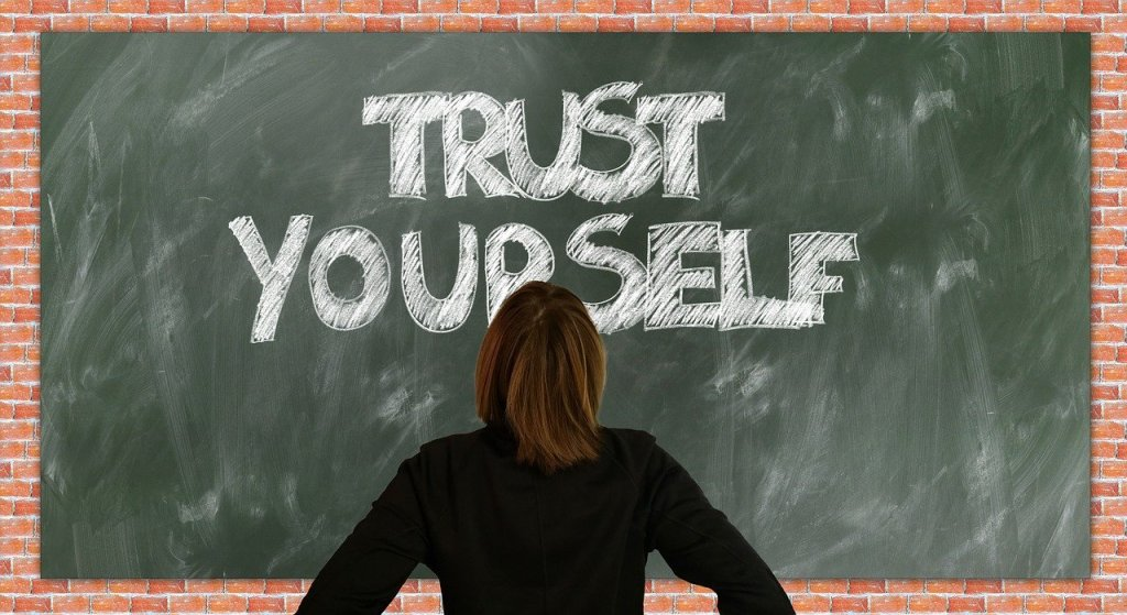 Woman facing a chalkboard which reads Trust Yourself