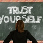 Woman facing a chalkboard that reads Trust Yourself