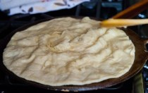 2-as you see it browning, flip to cook both sides; the start to draw the pratha into the centre of the tawa to cook the edges
