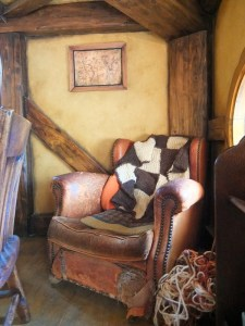 The Green Dragon. A comfy chair with blankets in corner of room with wood and yellow walls