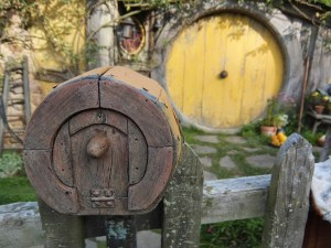 Hobbit letterbox. A round letterbox with yellow hobbit door in background.