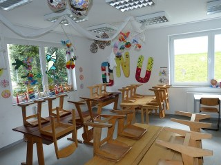 Most Gifted Children Have Never Been Studied | yellowreadis.com  Image: Children's classroom, wooden chairs on wooden tables with bunting and pictures on walls and roof