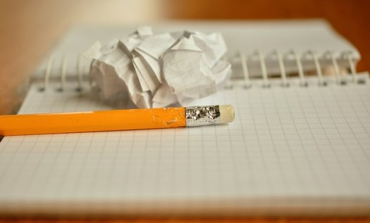 Image: Chewed yellow pencil with rubber and scrunched paper on notebook