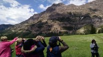 group looking through binoculars at a cliff face