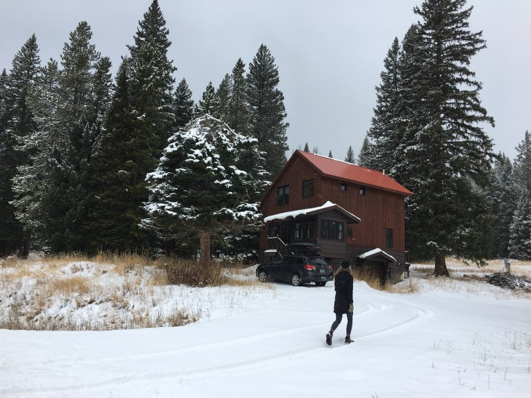 person walking up to cabins for rent near yellowstone