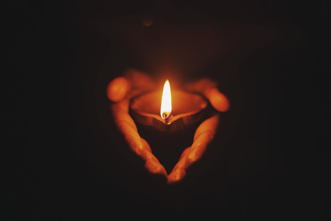 two-hands-holding-a-candle