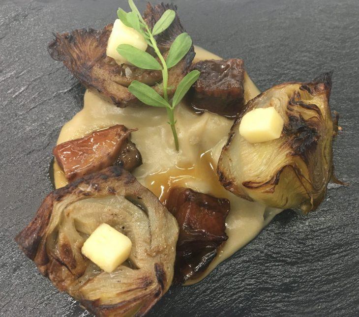 Alcachofa confitada sobre parmentier, lengua de vaca y queso afinado