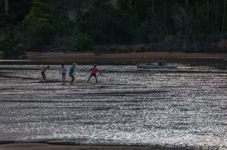 Kids playing in the river while a fisherman does his stuff.