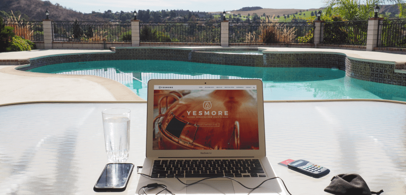 Remote Working from a laptop overlooking a pool in California USA