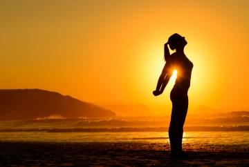 Yoga stretch on beach at sunset