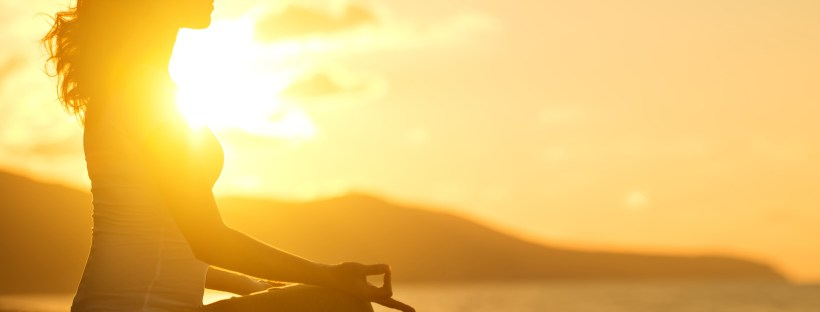 woman meditating on beach sunrise