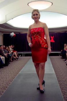 Trisha is wearing a strapless, red dragonfly dress with an asymmetrical peplum and pencil skirt.