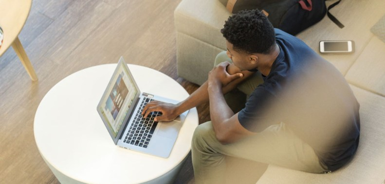 A young man looking at the LinkedIn homepage on his laptop screen.