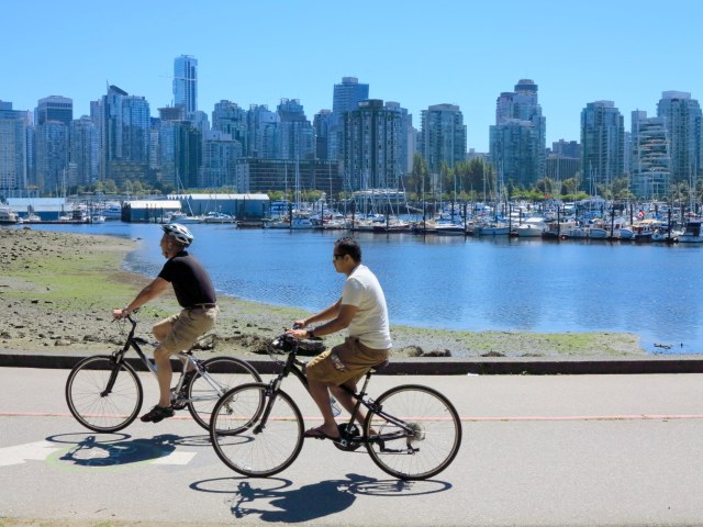 On a summer day in Vancouver, two bikers pass Beaver Lake in Stanley Park and head for the Seawall.