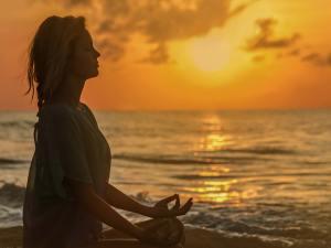 a woman peacefully meditating at the beach