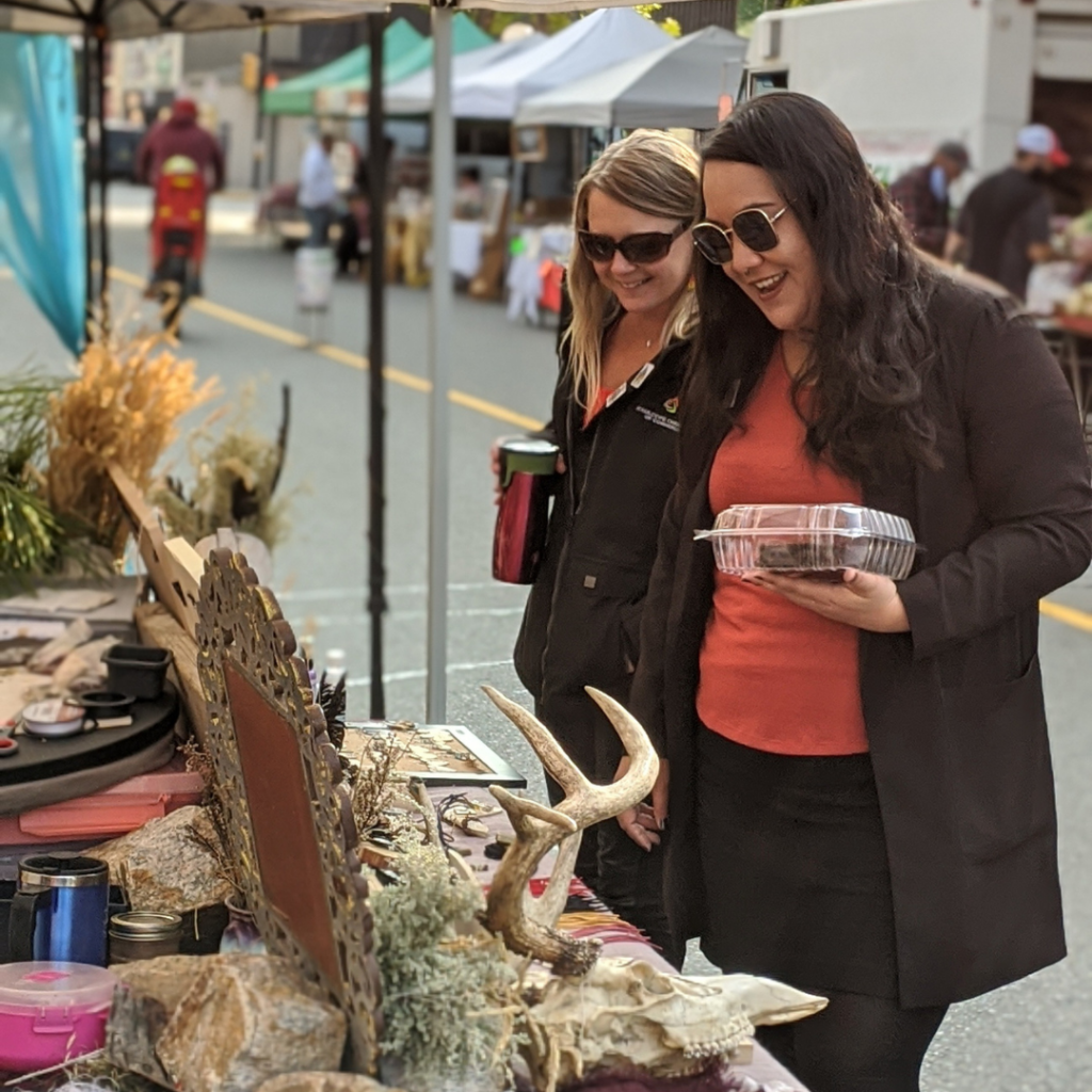 Acacia and Deanna of the Kamloops Chamber of Commerce walking through theKamloops Regional Farmers' Market.