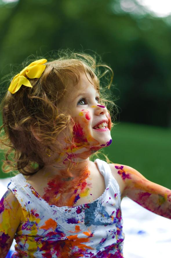 Spread happiness depicted by smiling girl child with colorful paint on her dress and body