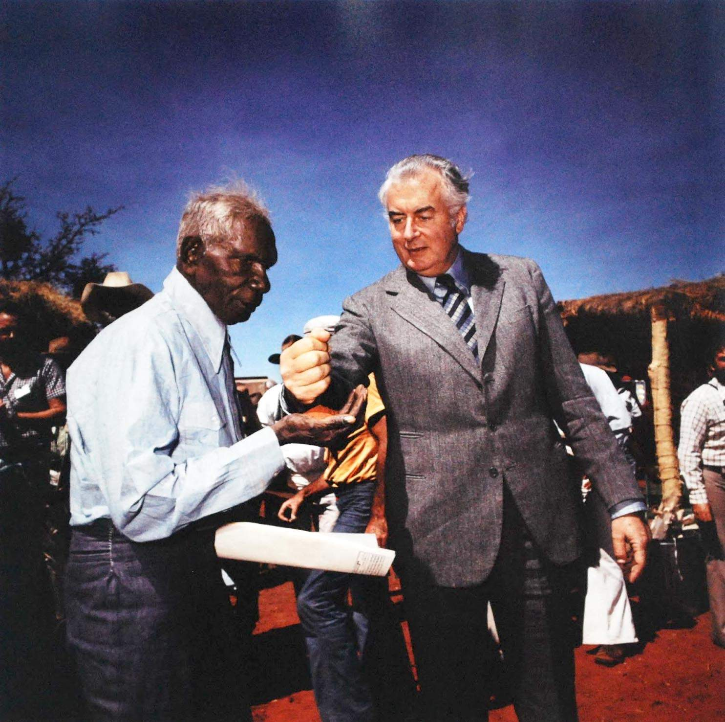 Vincent Lingiari accepts a handful of the Centre's red sand from Prime Minister Gough Whitlam