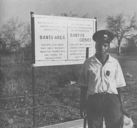 """בימי שלוט האפרטהייד: שוטר שחור נראה ליד שלט, המכריז (באנגלית ובאפריקאנס) """"איזור באנטו"""". השלט הזה מציין את גבול הבנטוסטן של לֶבּוֹאַה(Lebowa), בפינה הצפונית של דרום אפריקה, ליד הגבול הבין לאומי עם בוצוואנה וזימבאבווה                      מקור: South Africa: a Country Study, בהוצאת מחלקת החקר של ספריית הקונגרס, וושינגטון, 1997"""