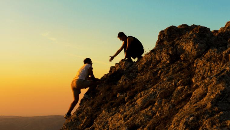 山登りで助け合う人